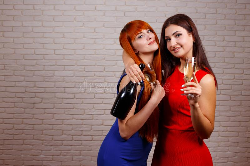 Två attraktiva gladlynta flickor som dansar, har roligt och dricker c royaltyfri foto