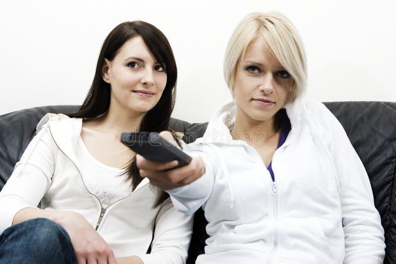 Två attraktiva kvinnliga vänner som håller ögonen på television royaltyfria bilder