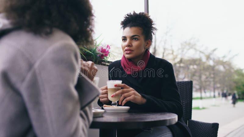 Två attraktiva kvinnor för blandat lopp som talar och dricker kaffe i gatakafé Vänner har gyckel, når de har besökt galleriaförsä arkivfoto