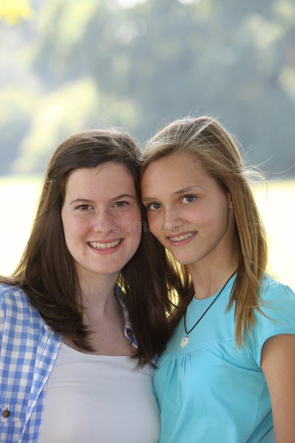 Två attraktiva le unga tonårs- flickor arkivbilder