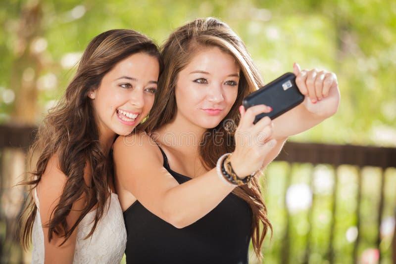 Två attraktiva tonåriga flickvänner för blandat lopp tar Selfies med den smarta telefonen arkivfoto