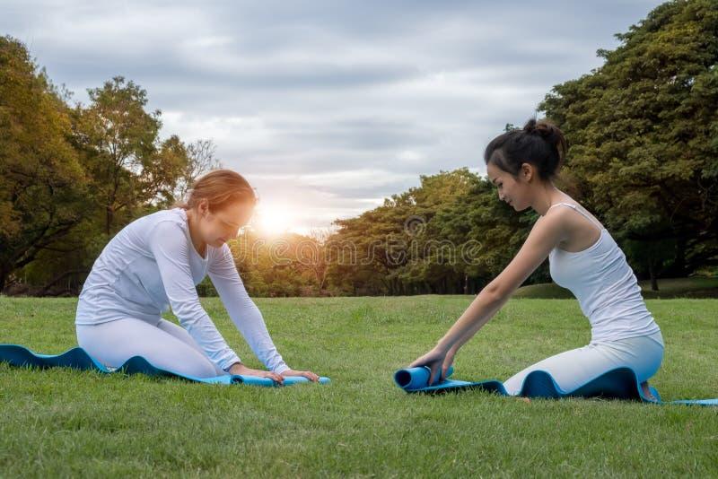 Två attraktiva unga kvinnor som viker blå matt afte för yoga eller för kondition royaltyfri foto
