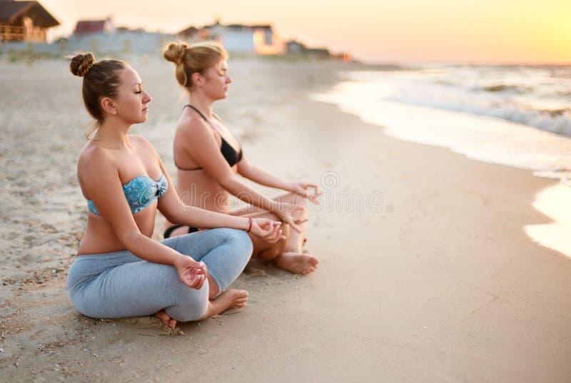 Två autentiska kvinnor som gör gruppyogameditation på stranden på soluppgång Flickor som kopplar av i lotusblomma, poserar asana  arkivfoton