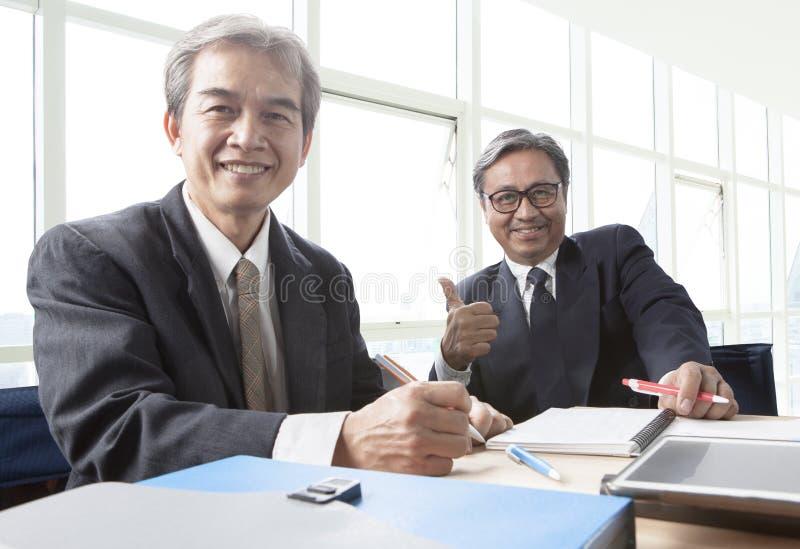 Två av den asiatiska toothy le framsidan för affärsman och att koppla av i offic royaltyfria foton