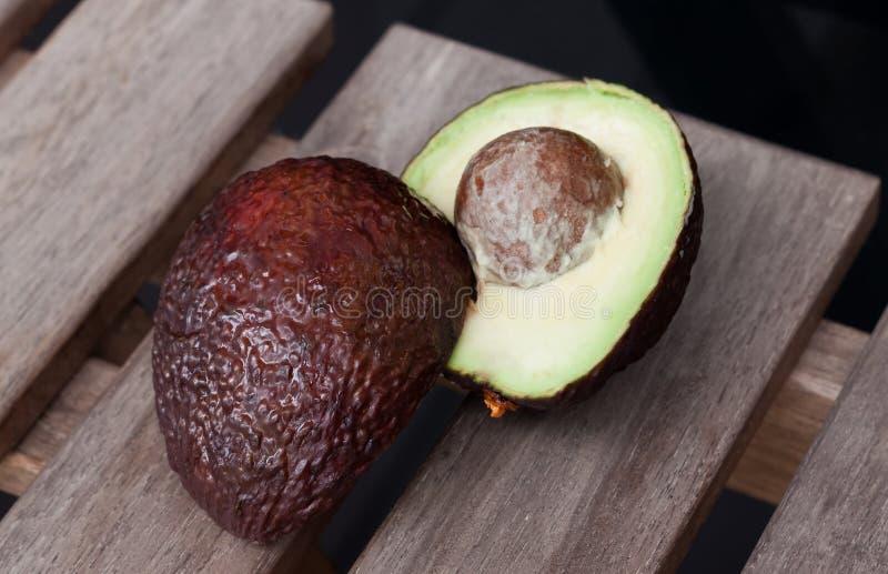 Två avokadohalvor på en träbakgrund royaltyfria bilder