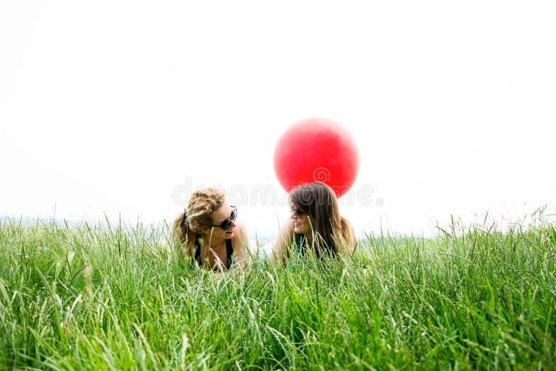 Två bästa flickavänner som lägger på gräset royaltyfri foto