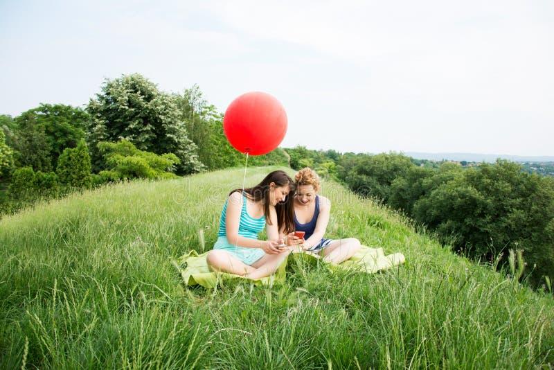 Två bästa flickavänner som sitter på gräset royaltyfri foto