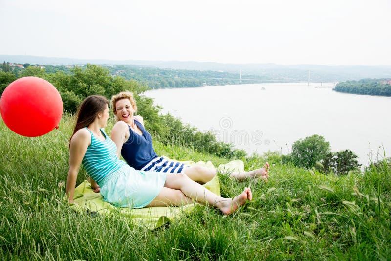 Två bästa flickavänner som sitter på gräset arkivfoton