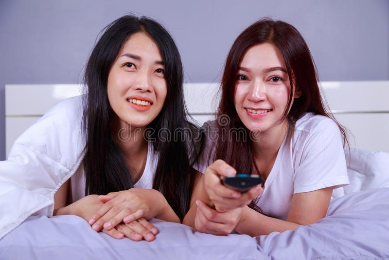 Två bästa vän som håller ögonen på tv med fjärrkontrollen på säng i sovrum arkivbilder