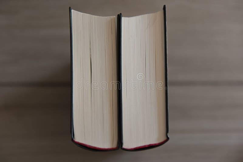 Två böcker står på en wood bakgrund arkivfoton