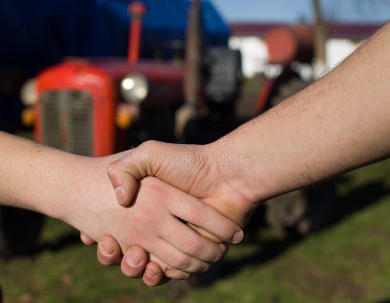 Två bönder som skakar händer på lantgård fotografering för bildbyråer