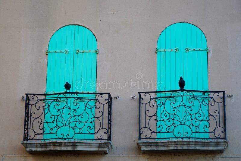Två balkonger, två fåglar, två vikande slutare royaltyfri bild