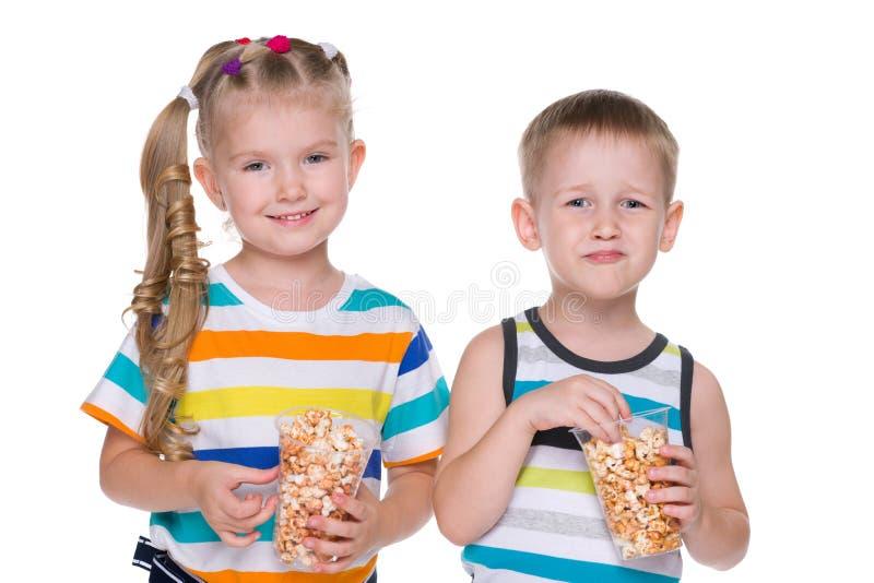 Två barn äter popcorn arkivbild