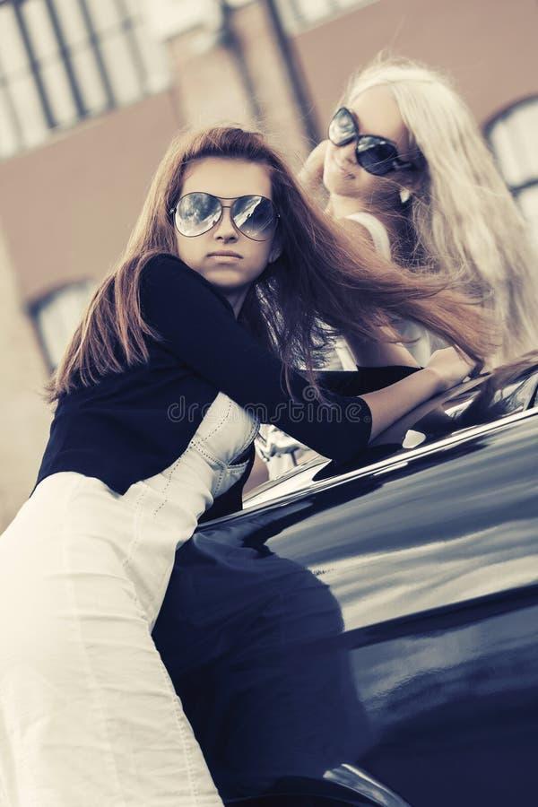 Två barn danar kvinnor som lutar på tappningbilen i stadsgata royaltyfria foton