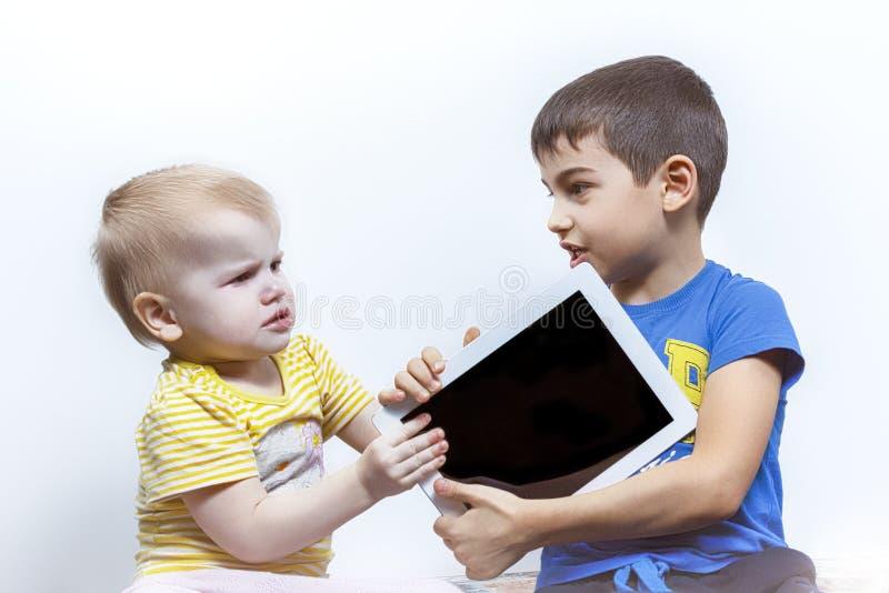 Två barn grälar, på grund av minnestavlaPC:N, barns konflikt royaltyfria bilder