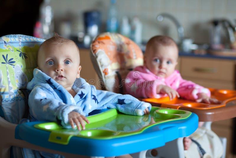 Två barn i ämbetsdräkter i hög stol arkivfoton