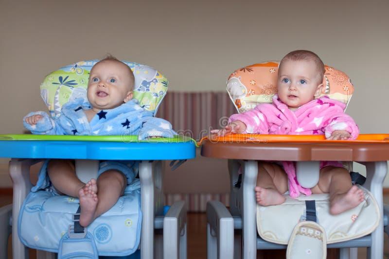 Två barn i ämbetsdräkter i hög stol inomhus fotografering för bildbyråer