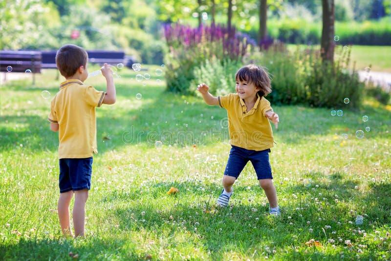 Två barn i parkera som blåser och jagar såpbubblor och mummel royaltyfria foton