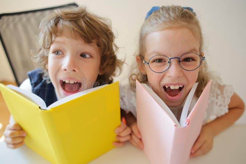 Två barn klasskompis, pojke och flicka, sitter på det samma skrivbordet arkivbilder
