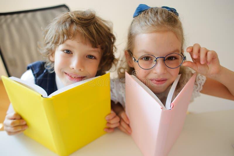 Två barn klasskompis, pojke och flicka, sitter på det samma skrivbordet royaltyfri bild