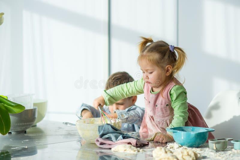 Två barn lagar mat något från degen arkivbilder
