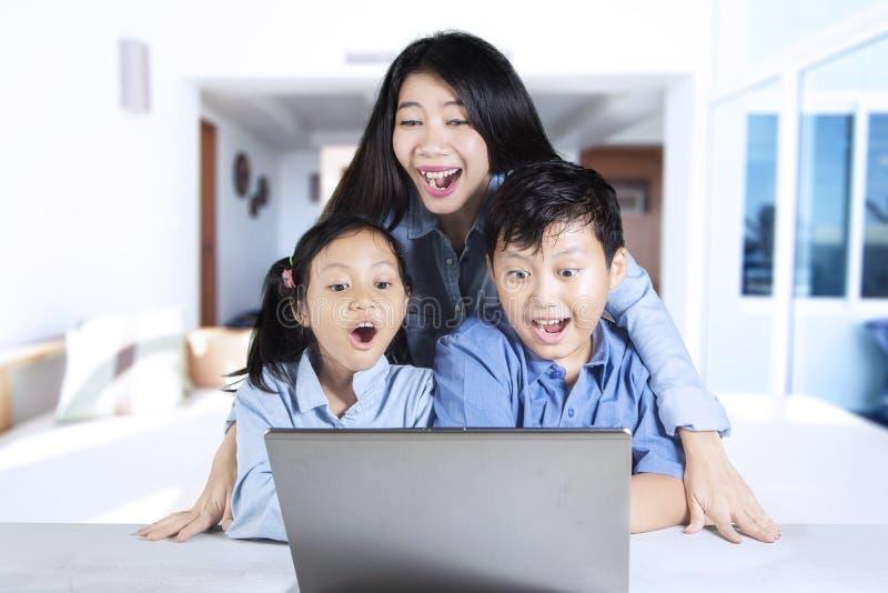 Två barn och moder som ser bärbara datorn arkivbild