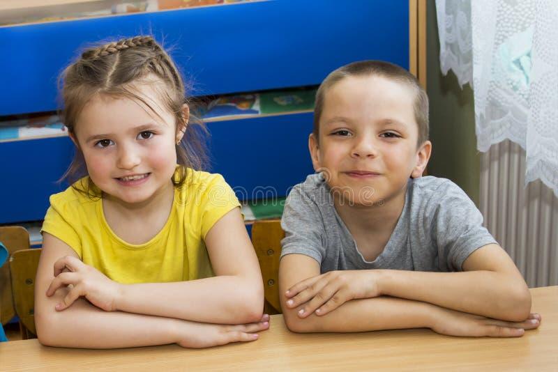 Två barn på tabellen gulliga grundskolaungar i ett klassrum En pojke och en flicka sitter på tabellen St?ende av royaltyfri fotografi