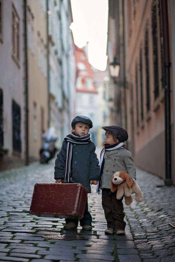 Två barn, pojkebröder, bärande resväska och hundleksak, lopp i staden bara royaltyfri foto