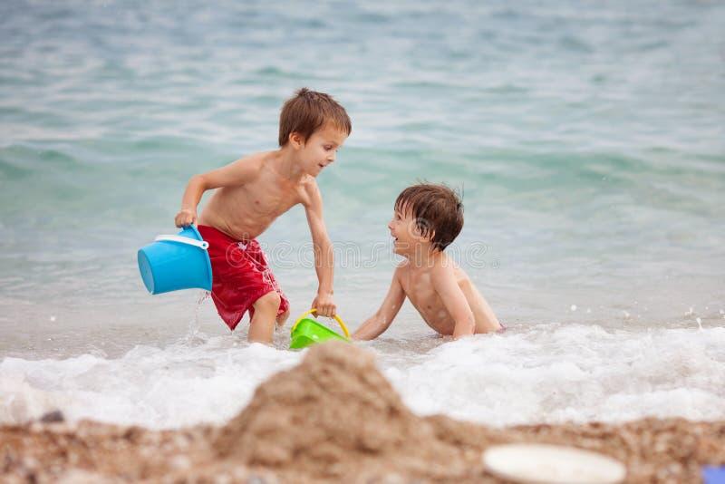 Två barn, pojkebröder som spelar på stranden med sandleksaker royaltyfri fotografi