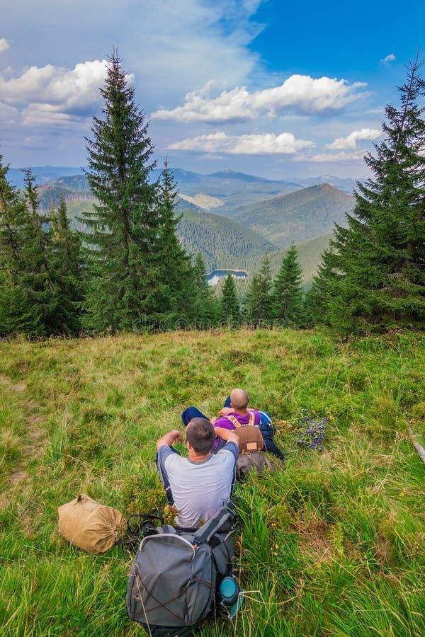 Två barn som är turist- i berg som vilar Synevyr Carpathians, Ukraina royaltyfria bilder