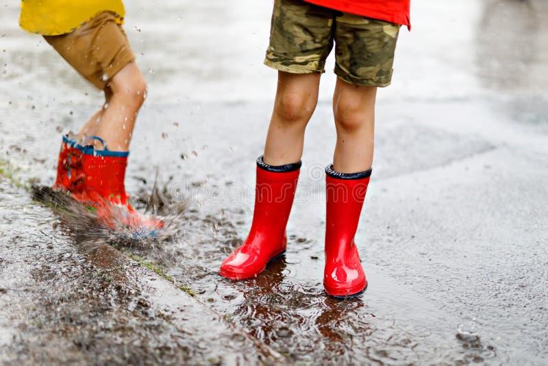Två barn som bär röda regnkängor som hoppar in i en pöl arkivbilder
