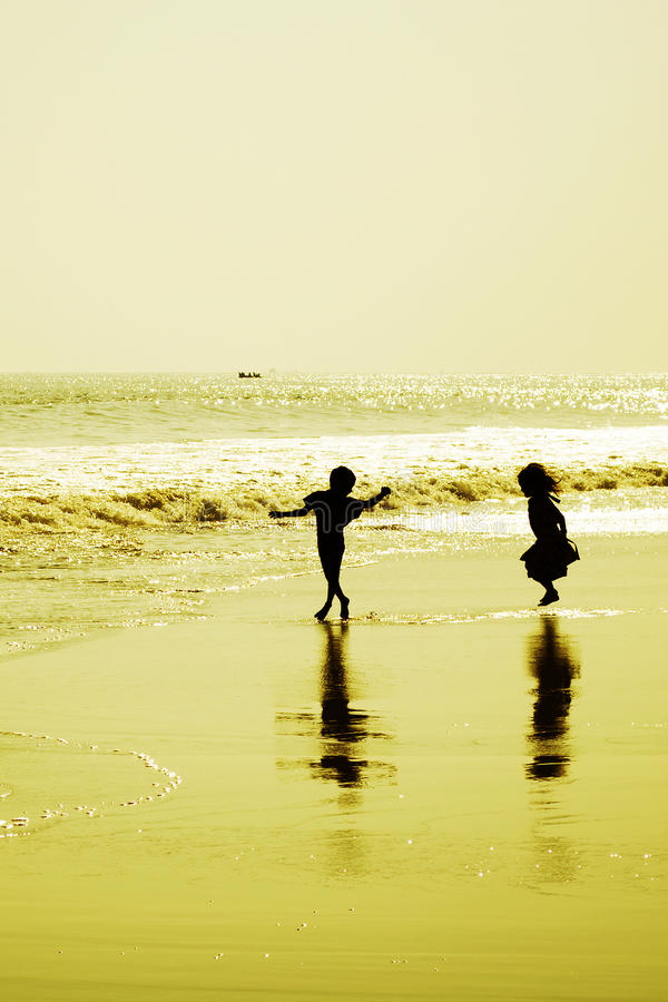 Två barn som dansar på stranden på solnedgången royaltyfri bild