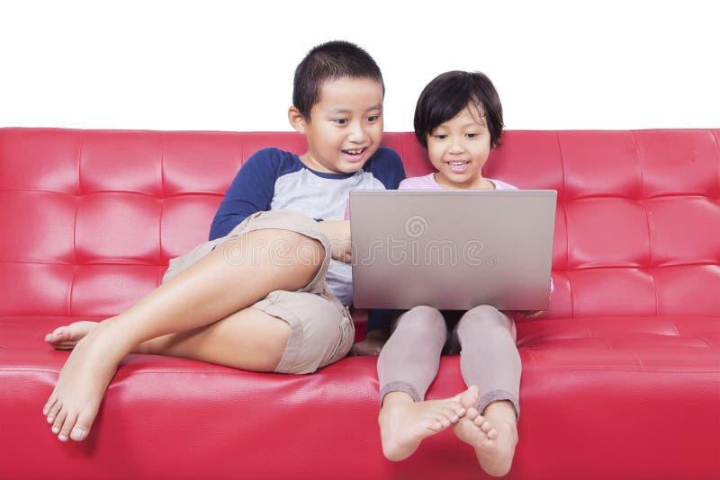 Två barn som håller ögonen på film samman med bärbara datorn royaltyfria bilder