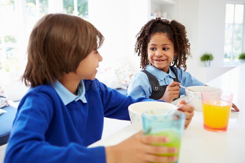 Två barn som har frukosten för skola i kök arkivfoto
