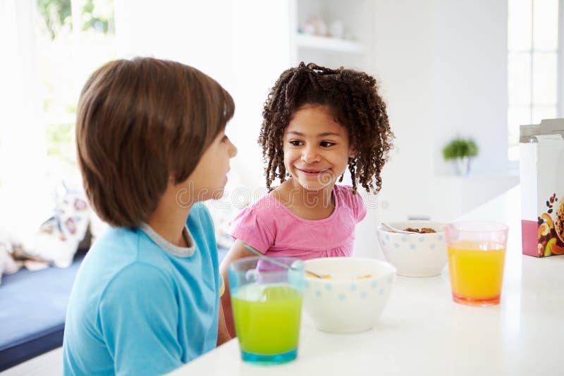 Två barn som har frukosten i kök tillsammans fotografering för bildbyråer