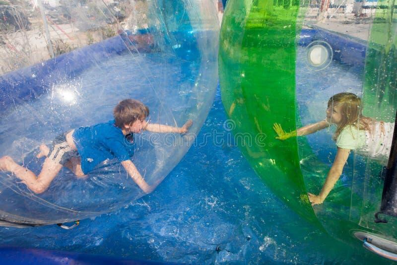 Två barn som har gyckel i en uppblåsbar plast- ballong på arkivbilder