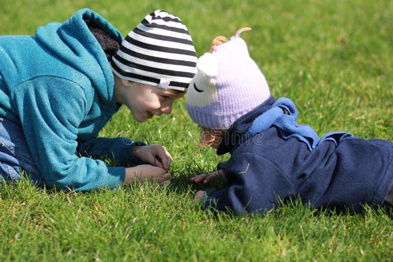Två barn som ligger på gassna, head rörande huvud- och hagyckel som ser de arkivbild
