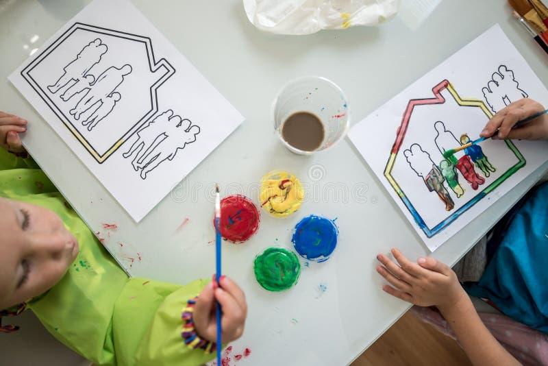 Två barn som målar en skissa av en familj i ett hus royaltyfria bilder