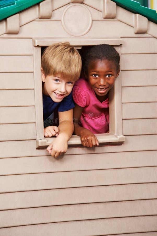 Två barn som ser till och med fönster i lekstuga arkivbilder