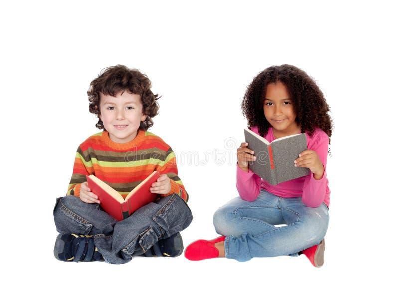 Två barn som sitter på golvläsningen arkivbilder