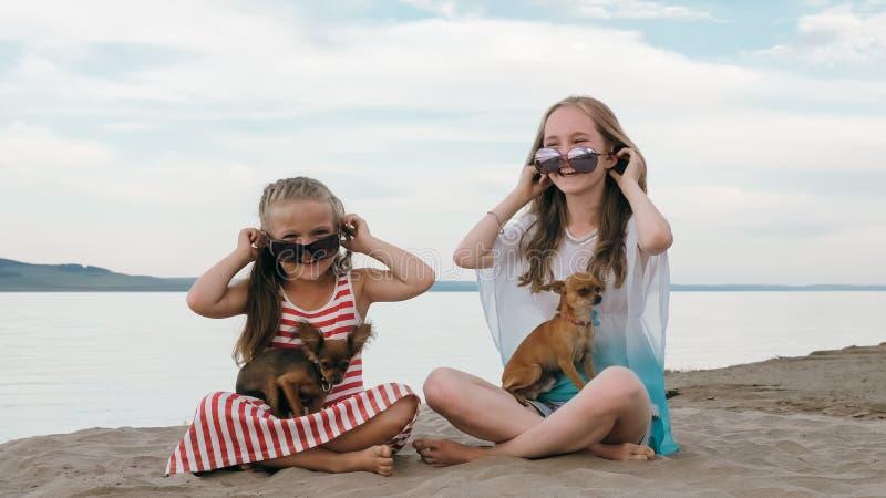 Två barn som spelar som hundkapplöpning på sanden på stranden arkivbild