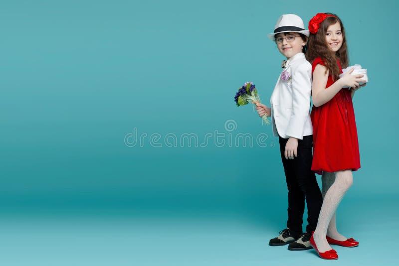 Två barn som tillbaka står för att dra tillbaka, pojke i dräkt, hatt och flicka i röd klänning i studion som isoleras på turkosba arkivbild