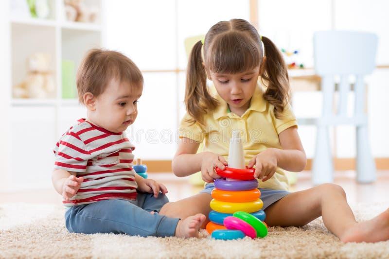 Två barn tillsammans Storasystern hjälper det mer ung för att montera leksakpyramiden royaltyfri bild