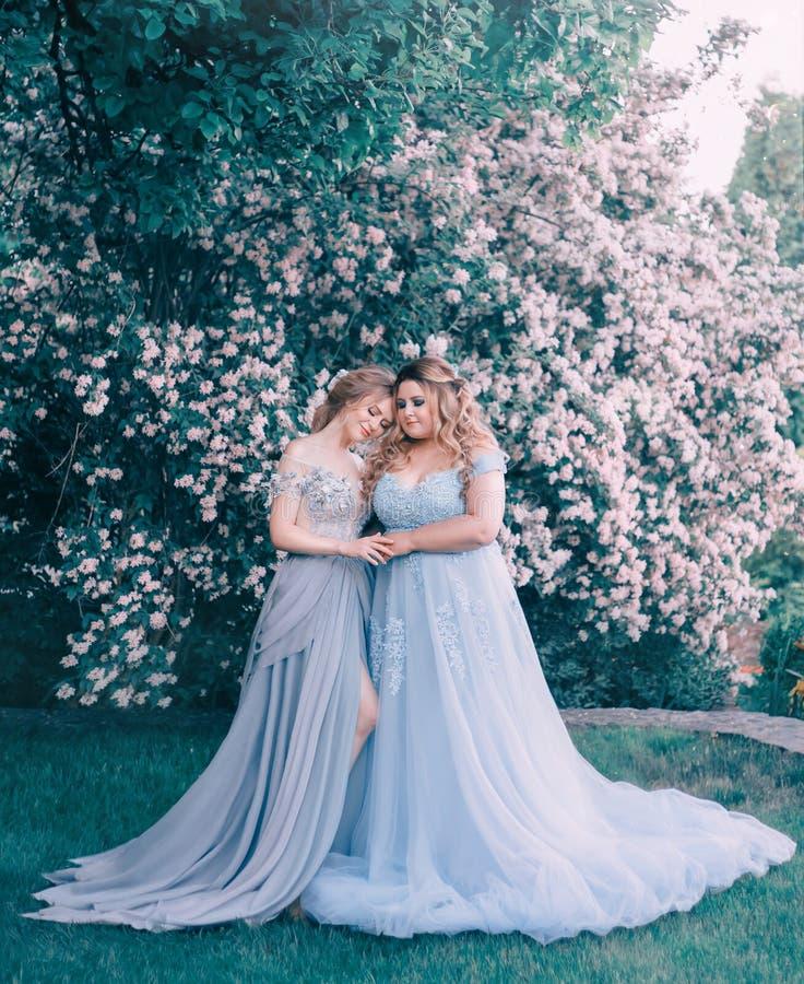 Två barn, vuxna kvinnor kramar sig mot bakgrunden av ett blomningträd, en sagolik trädgård Prinsessa in fotografering för bildbyråer