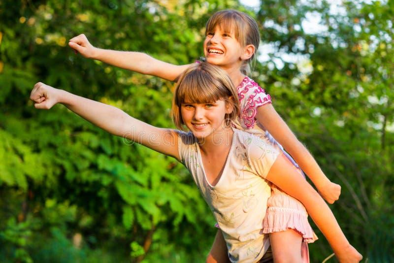 Två barnflickor som tillsammans spelar Systrar spelar superheroen Lyckliga ungar som har gyckel, att le och att krama royaltyfri foto