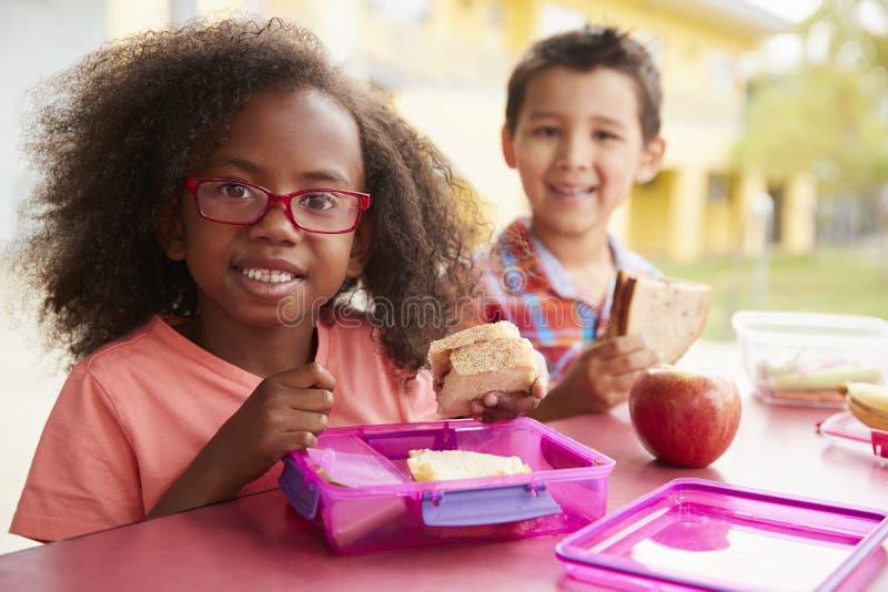 Två barnskolaungar som tillsammans äter deras matsäckar royaltyfri bild
