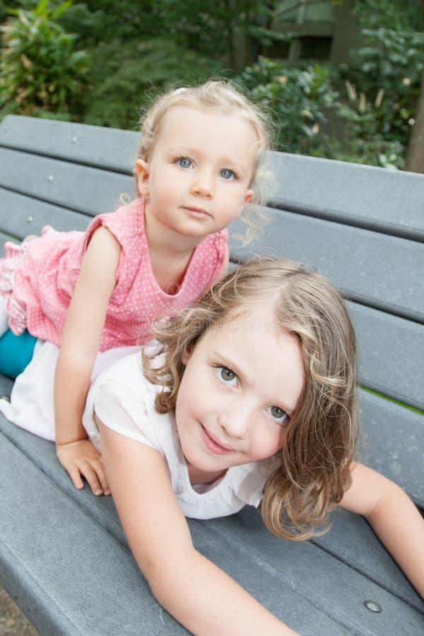 Två barnsysterflickor som ligger på den wood bänken, spelar gyckel och förälskelse royaltyfri foto