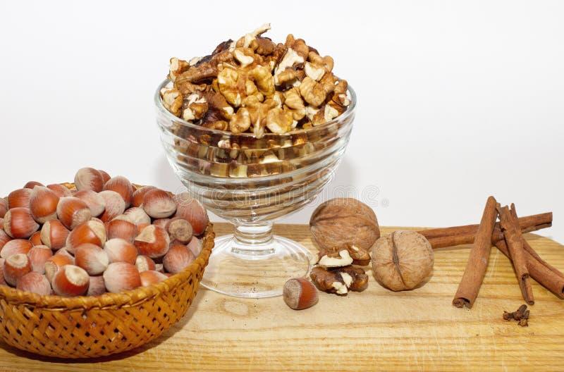 Två behållare med hasselnötter och valnötter och flera pinnar av kanel på vit bakgrund fotografering för bildbyråer