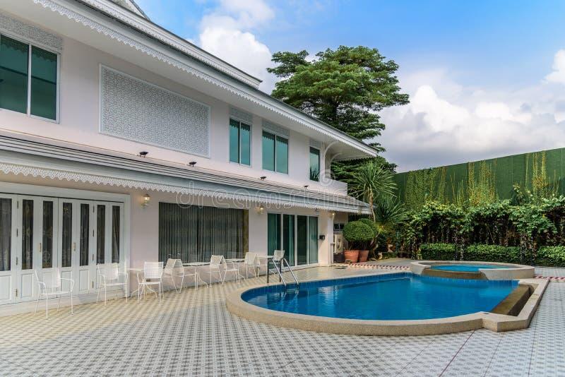 Två-berättelse hus med staketet och simbassängen arkivfoto