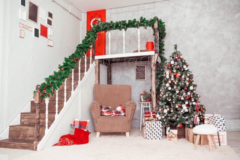 Två-berättelse rum i en klassisk stil för nytt år med en stor stol och en julgran royaltyfri bild
